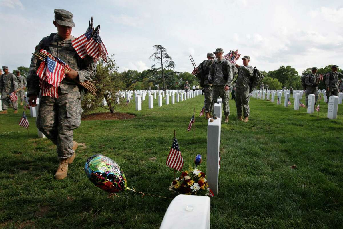 """Walking past a grave with a """"happy birthday"""" balloon on it, soldiers with the 3rd U.S. Infantry Regiment, or """"Old Guard,"""" check Section 60 to make sure each grave has a flag in honor of Memorial Day, during the annual """"Flags-In"""" at Arlington National Cemetery in Arlington, Va., on Thursday, May 24, 2012."""
