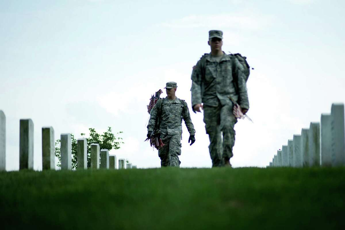 Soldiers carry flags through Arlington National Cemetery May 24, 2012 in Washington, DC, ahead of Memorial Day to be marked on May 28, 2012.