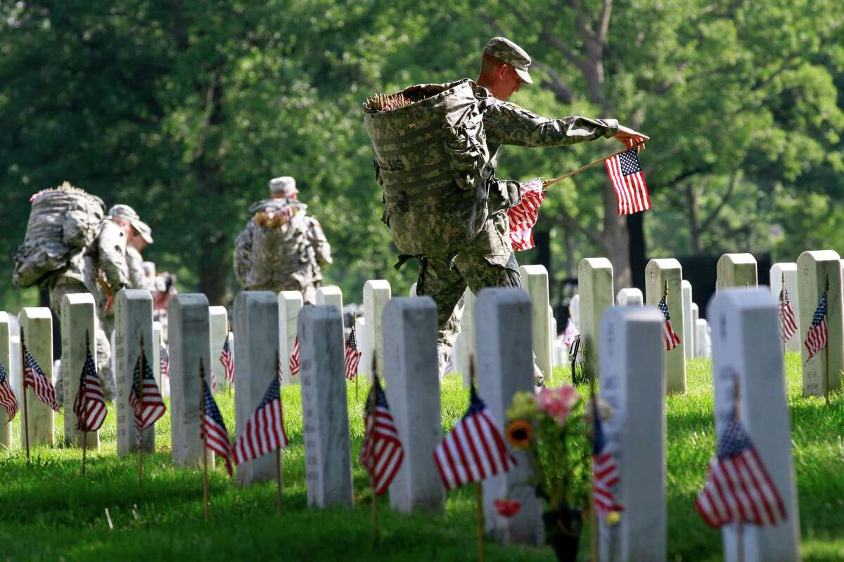 """Army Sgt. Brian Ellis, 22, of Canyon Lake, Texas, a soldier with the 3rd U.S. Infantry Regiment, or """"Old Guard,"""" places a flag before each grave in preparation for Memorial Day, during the annual """"Flags-In"""" at Arlington National Cemetery in Arlington, Va., on Thursday, May 24, 2012."""