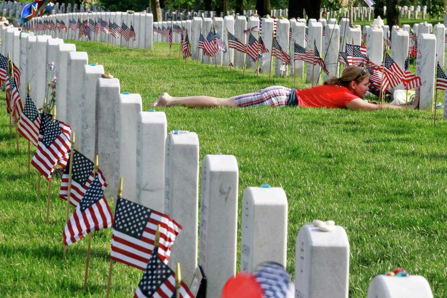 "Air Force Major Terry Dutcher, of Hill Air Force Base, Utah, touches the headstone of her son, Army Corporal Michael Avery Pursel, who died serving in Iraq in 2007 at age 19, surrounded by flags placed by soldiers at each grave for the annual ""Flags-In"" in honor of Memorial Day, at Arlington National Cemetery in Arlington, Va., on Thursday, May 24, 2012. Photo: Jacquelyn Martin, Associated Press / AP"
