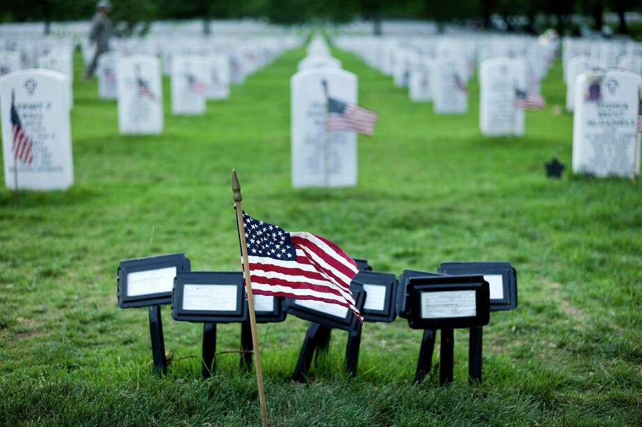 A flag is seen at the temporary marker for a mass grave in Section 60, an area largely used for those who died while serving in the wars in Afghanistan and Iraq. Photo: BRENDAN SMIALOWSKI, AFP/Getty Images / 2012 Brendan Smialowski