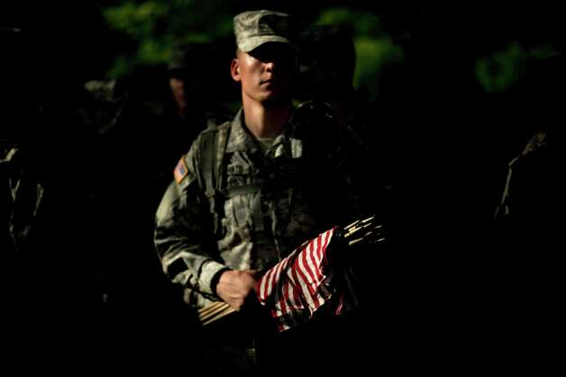 A soldier holds flags at Section 60, an area largely used for those who died while serving in the wars in Afghanistan and Iraq.  Members of the US Army's Old Guard and others participated in the yearly event where small American flags are placed at over 220 thousand headstones in the cemetery reserved for members of the US military and those who served America. Photo: BRENDAN SMIALOWSKI, AFP/Getty Images / 2012 Brendan Smialowski