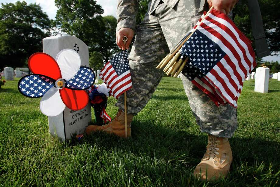 "In Section 60, where many of the soldiers who fought in Iraq and Afghanistan are buried, Captain James Leggett, of Alexandria, Va., with the 3rd U.S. Infantry Regiment, or ""Old Guard,"" places flags before each grave in preparation for Memorial Day. Photo: Jacquelyn Martin, Associated Press / AP"