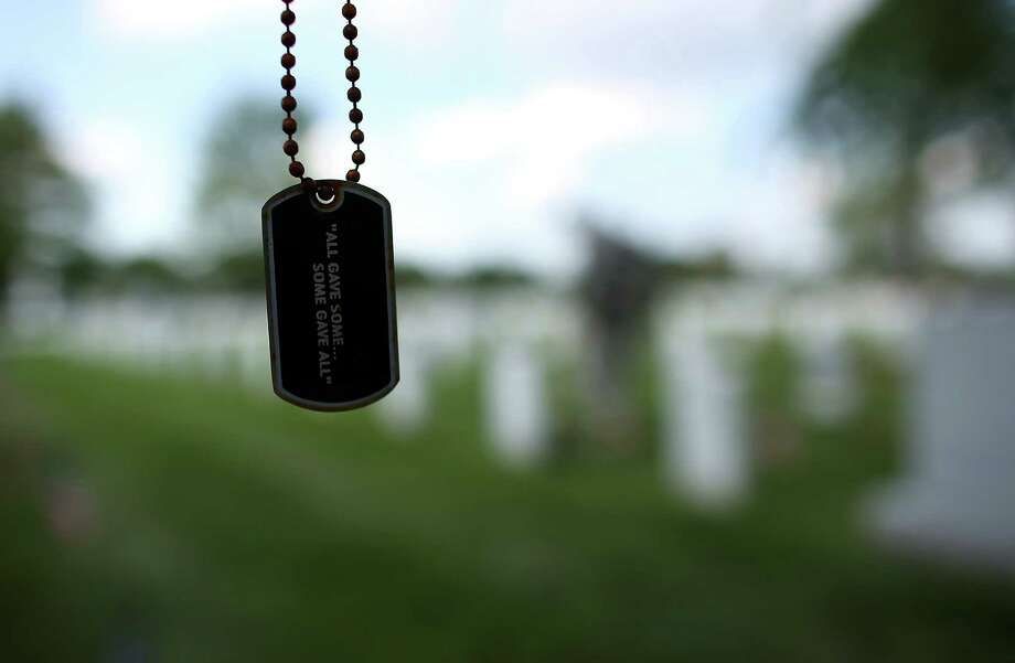 A dogtag hangs from a tree branch as members of the 3rd U.S. Infantry Regiment place American flags at the graves of U.S. soldiers buried in Section 60 at Arlington National Cemetery. Photo: Win McNamee, Getty Images / 2012 Getty Images