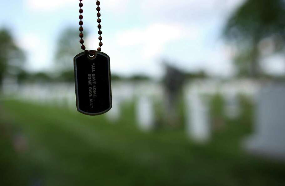 A dogtag hangs from a tree branch as members of the 3rd U.S. Infantry Regiment place American flags