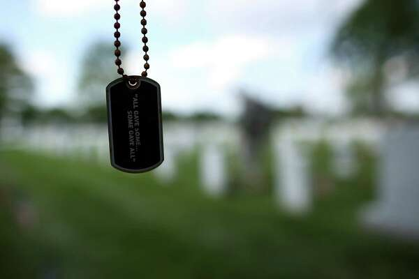 A dogtag hangs from a tree branch as members of the 3rd U.S. Infantry Regiment place American flags at the graves of U.S. soldiers buried in Section 60 at Arlington National Cemetery.