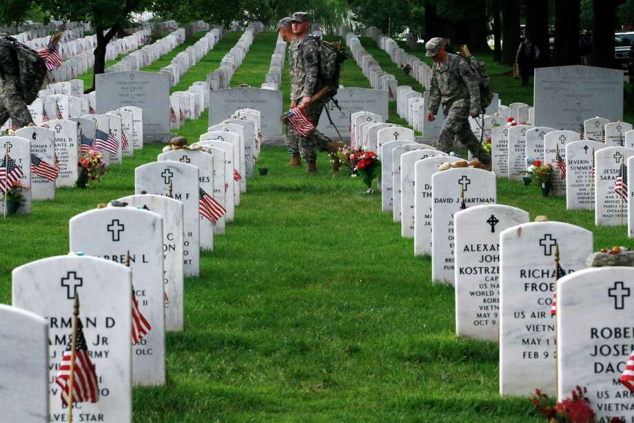 "Soldiers with the 3rd U.S. Infantry Regiment, or ""Old Guard,"" check Section 60 to make sure each grave has a flag in honor of Memorial Day, during the annual ""Flags-In"" at Arlington National Cemetery in Arlington, Va., on Thursday, May 24, 2012. Photo: Jacquelyn Martin, Associated Press / AP"