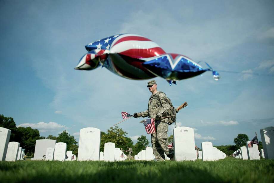 A soldier plants a flag at a grave in Section 60. Photo: BRENDAN SMIALOWSKI, AFP/Getty Images / 2012 Brendan Smialowski
