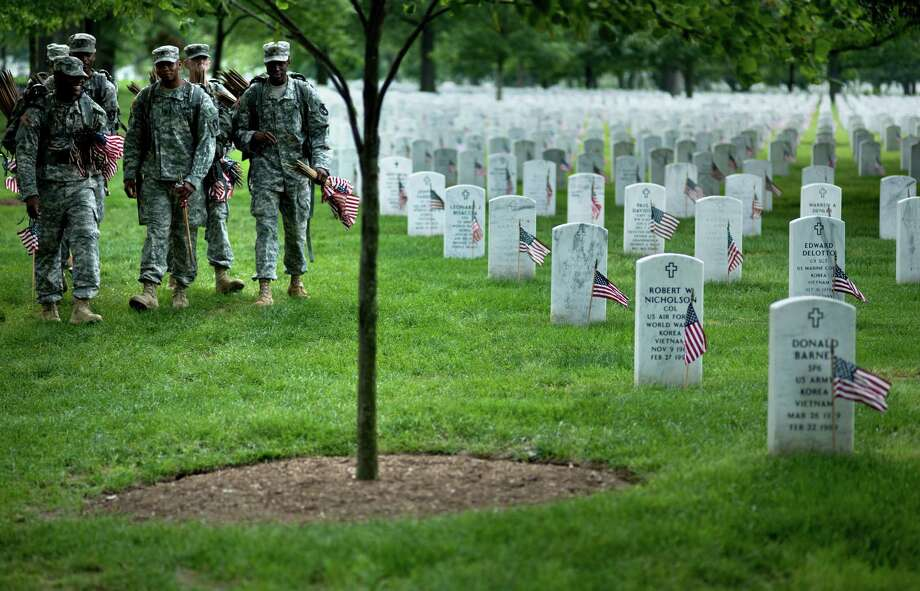 Soldiers arrive to plant flags at graves in Section 60. Photo: BRENDAN SMIALOWSKI, AFP/Getty Images / 2012 Brendan Smialowski