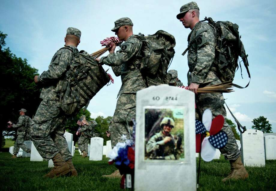 Soldiers pass the grave of US Army Lt. Thomas Brown, who served in Iraq and died in 2008. Photo: BRENDAN SMIALOWSKI, AFP/Getty Images / 2012 Brendan Smialowski