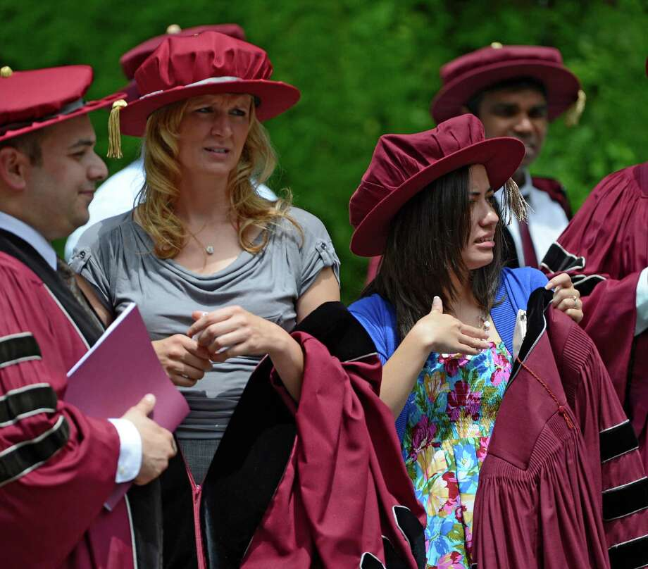 New Medical Doctors Aimee Steiniger, left and Shelby Spandl keep cool by keeping their robes lowered while waiting for the Albany Medical College graduation ceremony to commence at the Saratoga Performing Arts Center in Saratoga Springs, N.Y. May 24, 2012.  (Skip Dickstein / Times Union) Photo: SKIP DICKSTEIN / 00017189A