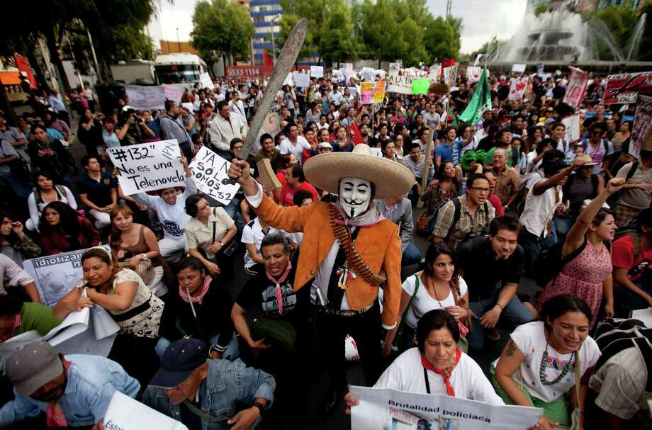 Some 15,000 protesters, including one wearing a Guy Fawkes mask, gather Wednesday in Mexico City to denounce the possible return of the old ruling Institutional Revolutionary Party, whose candidate is front-runner Enrique Peña Nieto. Photo: Eduardo Verdugo / AP