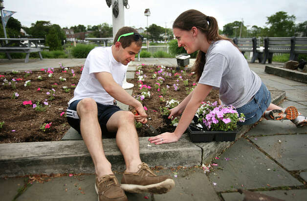 Summer employees Pat Benedosso, 20 of Milford, and Lucy Moye, 19 of Fairfield, plant hundreds of flowers at Lisman Landing Marina in Milford on Thursday, May 24, 2012. Photo: Brian A. Pounds / Connecticut Post