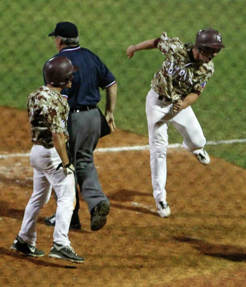 Kempner's Cody Criswell right, jumps in the air after scoring a run as teammate Jordan Kopelman left, looks on during the tenth inning of high school baseball playoff game against Cypress Creek at the University of Houston's Cougar Field Thursday, May 24, 2012, in Houston. Photo: James Nielsen, Chronicle / © Houston Chronicle 2012