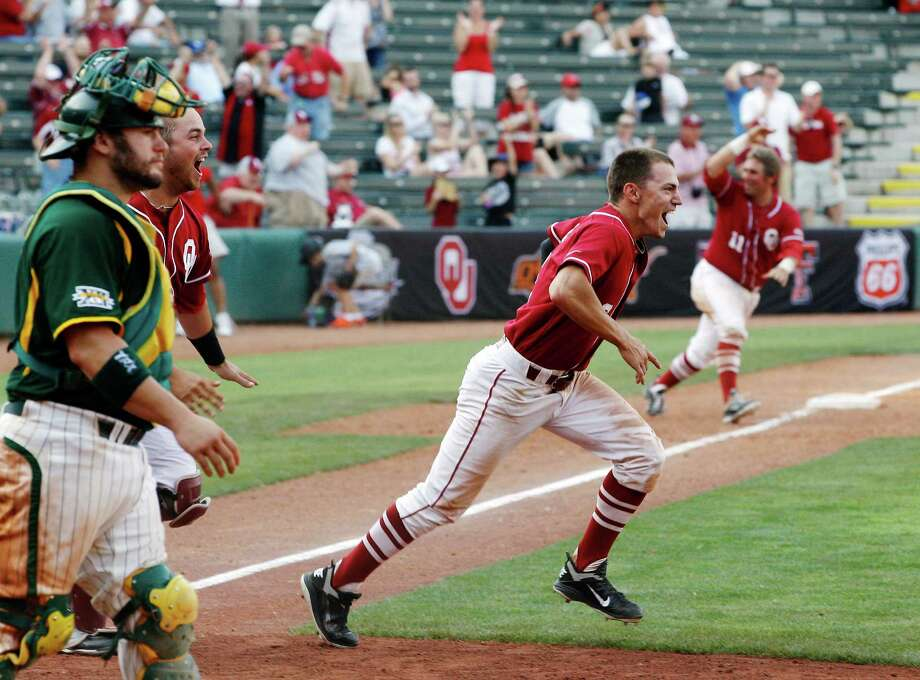 Oklahoma's Erik Ross (center), Tanner Toal (second from left) and Cody Reine (right) rush to celebrate the Sooners' walk-off victory over Baylor on Thursday. Photo: Sue Ogrocki / AP