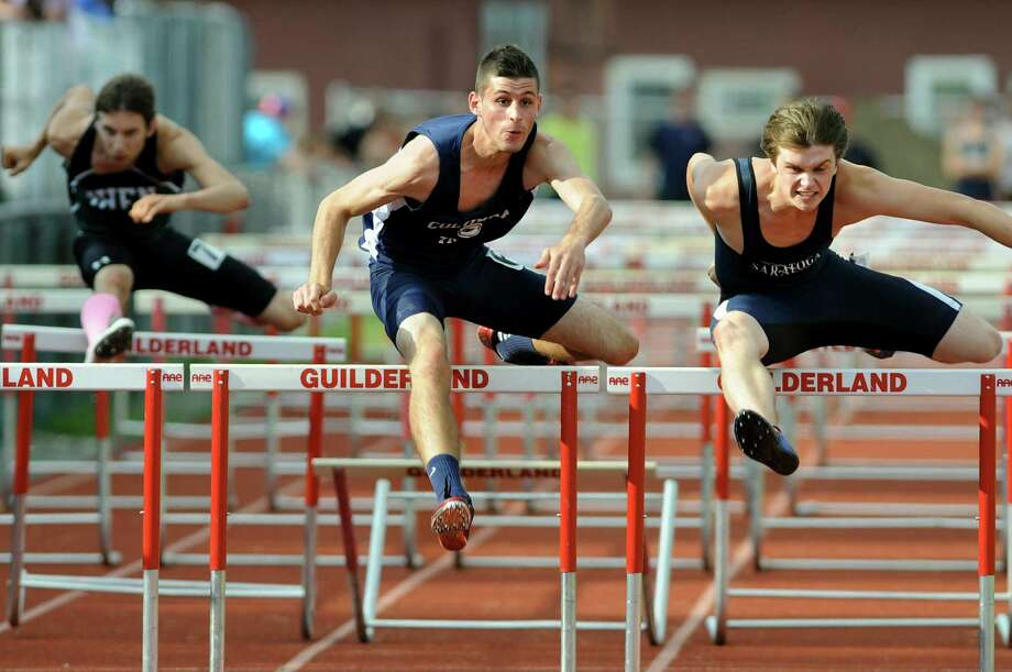 Columbia's Jake Alviene, center, and Saratoga's Steven Kuznia, right, are neck and neck into the final stretch of the 110-meter hurdles during the Section II boys track meet on Thursday, May 24, 2012, at Guilderland High in Guilderland, N.Y. Kuznia inched out Alviene to come in first. The two competitors will be roommates next year at SUNY Oneota. (Cindy Schultz / Times Union) Photo: Cindy Schultz / 00017784B