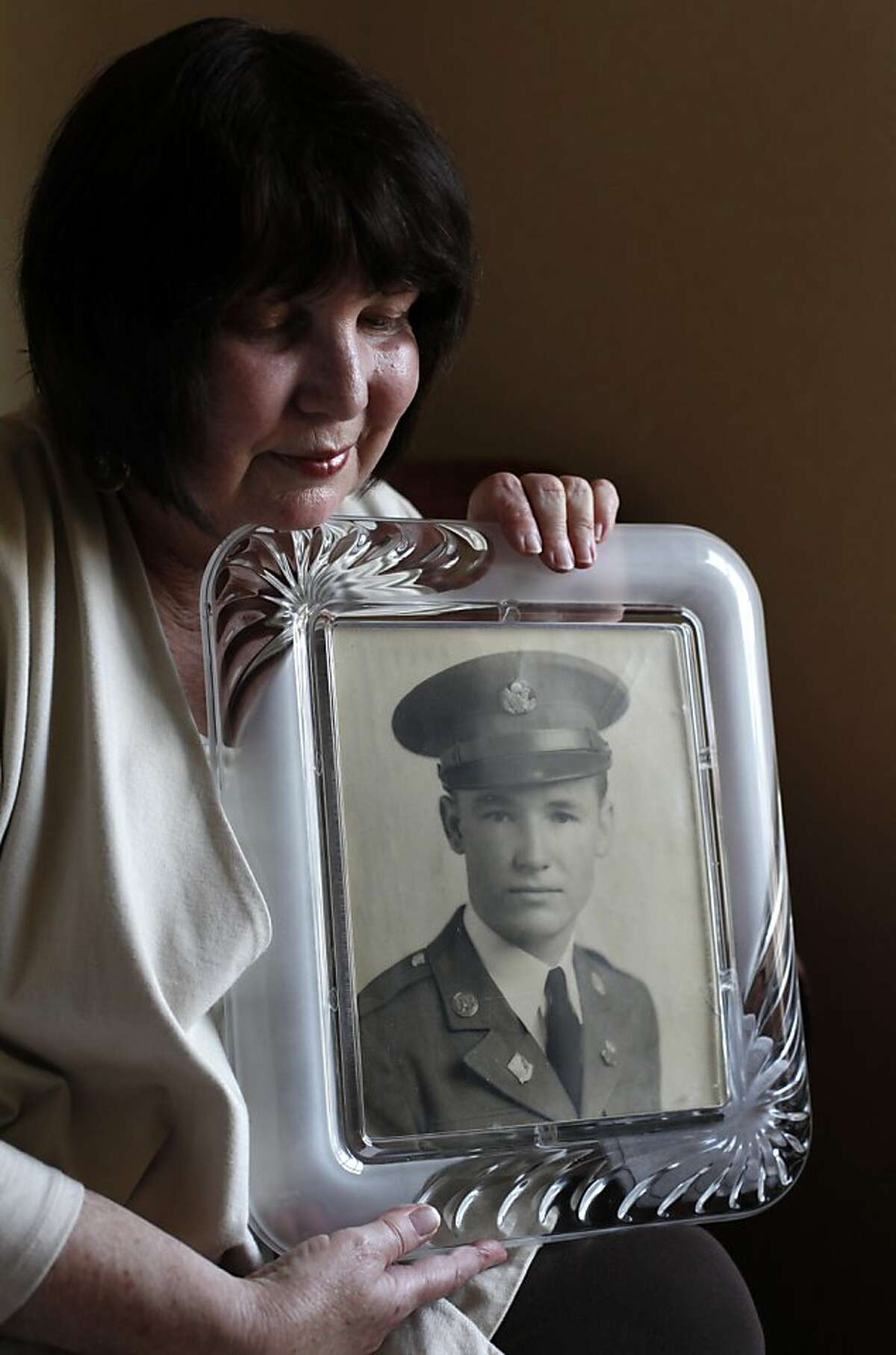 Betty Wheeler, of Citrus Heights, holds a photo of her father, Elbert Pollard, in San Francisco, Calif. Thursday, May 24, 2012. Pollard was a 28-year-old Air Force gunner in 1950 when he died parachuting out of a B-36. His remains were finally identified by DNA this year, and Friday they will be laid to rest in the Presidio.