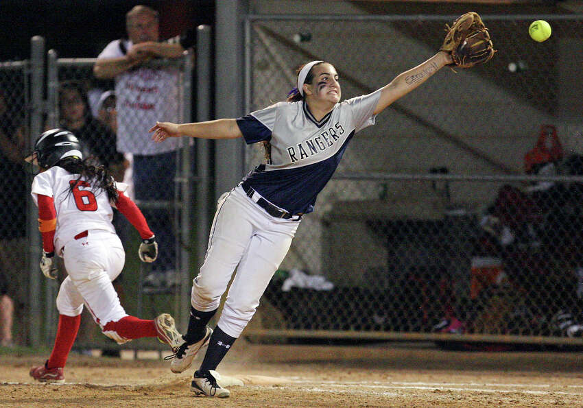 Smithson Valley's Taylor Darilek stretchs for the ball as New Braunfels Canyon's Brittney Gomez is safe at first in the ninth inning of their Region IV-4A final softball game Thursday, May 24, 2012 at NEISD Softball Complex. Smithson Valley won 7-5.