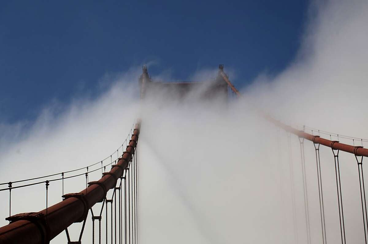 Wind of fog rush over the top of the north tower of the Golden Gate Bridge on May 8, 2012 in Marin, Calif.