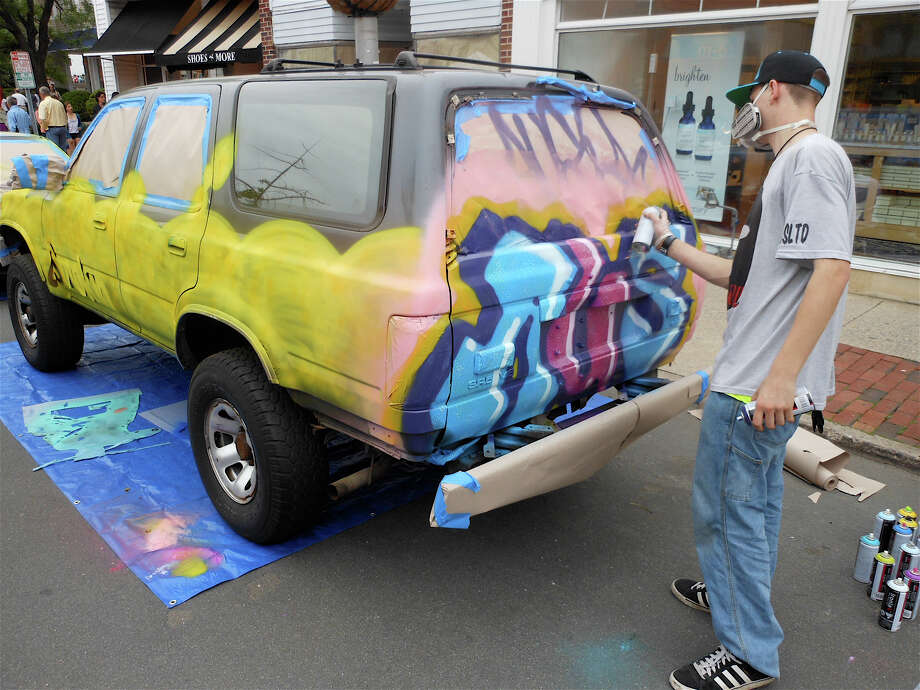 Austin Brodsky, an artist and clothes designer, graffiti tags a 4Runner at the Art About Town fest on Thursday evening in downtown Westport. Photo: Mike Lauterborn / Westport News contributed