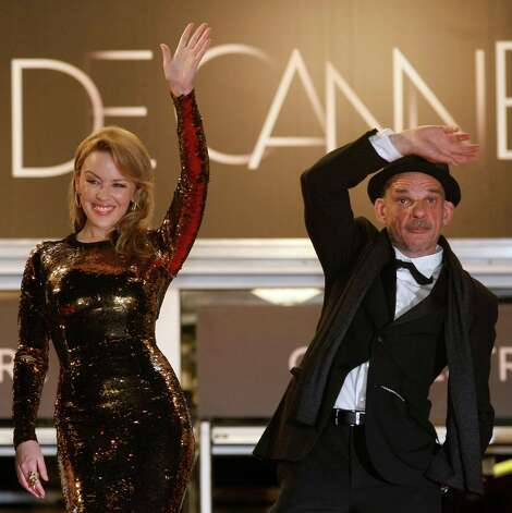 Actress Kylie Minogue, left, and actor Denis Lavant wave as they arrive for the screening of Holy Motors at the 65th international film festival, in Cannes, southern France, Wednesday, May 23, 2012.