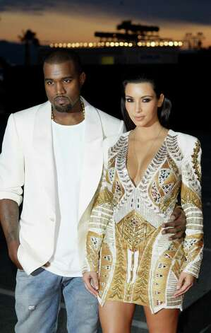 Singer Kanye West, left, and television personality Kim Kardashian arrive for the screening of Cruel Summer at the 65th international film festival, in Cannes, southern France, Wednesday, May 23, 201
