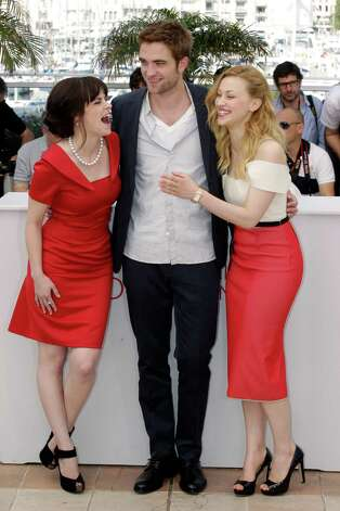 From left, actors Emily Hampshire, Robert Pattinson and Sarah Gadon pose during a photo call for Cosmopolis at the 65th international film festival, in Cannes, southern France, Friday, May 25, 2012.