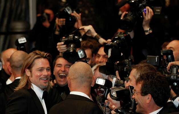 Actor Brad Pitt, left, surrounded by the photographers as he departs following the screening of Killing Them Softly at the 65th international film festival, in Cannes, southern France, Tuesday, May 2