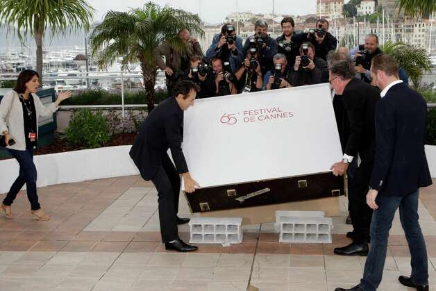 Actor Albert Dupontel, left, director Benoit Delepine and actor Benoit Poelvoorde take apart the plinth during a photo call for Le Grand Soir at the 65th international film festival, in Cannes, south