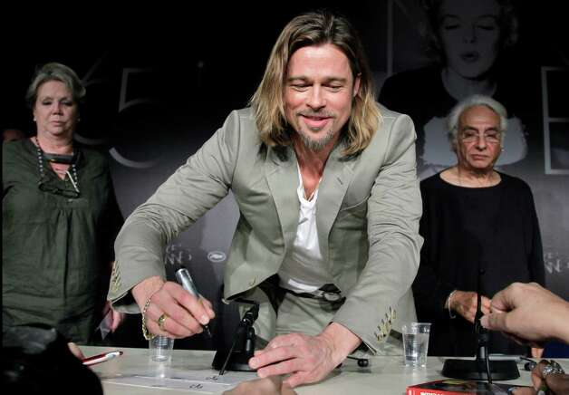 Actor Brad Pitt, centre signs an autograph during a press conference for Killing Them Softly at the 65th international film festival, in Cannes, southern France, Tuesday, May 22, 2012. Photo: Francoi