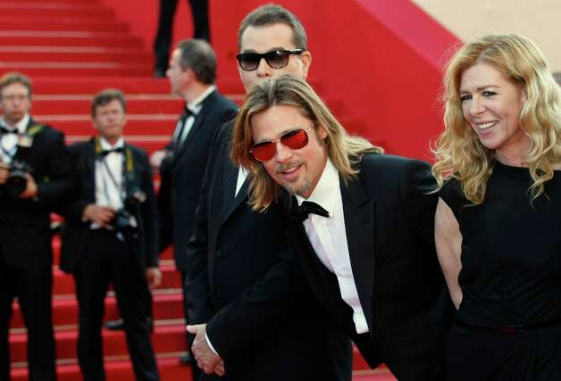 Actor Brad Pitt, center, actress Dede Gardner, right and actor Ray Liotta, partially seen arrive for the screening of Killing Them Softly at the 65th international film festival, in Cannes, southern