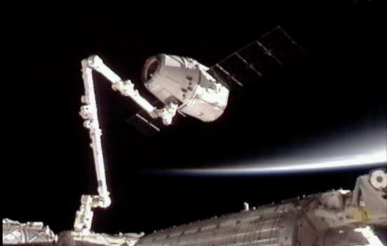 This image provided by NASA-TV shows the SpaceX Dragon commercial cargo craft, top, after Dragon was grappled by the Canadarm2 robotic arm and connected to the International Space Station, Friday, May 25, 2012. Dragon is scheduled to spend about a week docked with the station before returning to Earth on May 31 for retrieval. (AP Photo/NASA) Photo: Uncredited, Associated Press / NASA