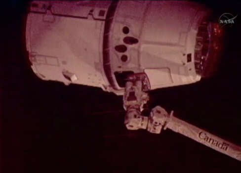 This image provided by NASA-TV shows the SpaceX Dragon commercial cargo craft, top, just after Dragon was grappled by the Canadarm2 robotic arm and connected to the International Space Station, Friday, May 25, 2012. Dragon is scheduled to spend about a week docked with the station before returning to Earth on May 31 for retrieval. (AP Photo/NASA) Photo: Uncredited, Associated Press / NASA