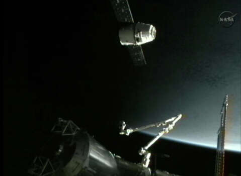 This image provided by NASA-TV shows the SpaceX Dragon commercial cargo craft, top, as Dragon approaches the International Space Station, Friday, May 25, 2012. Dragon is scheduled to spend about a week docked with the station before returning to Earth on May 31 for retrieval. (AP Photo/NASA) Photo: Uncredited, Associated Press / NASA