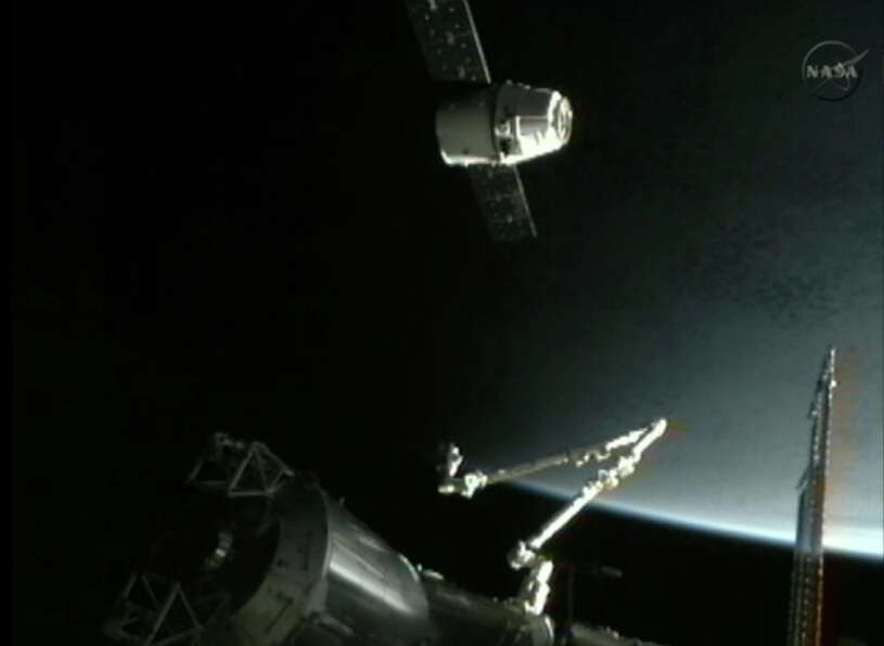 This image provided by NASA-TV shows the SpaceX Dragon commercial cargo craft, top, as Dragon approa