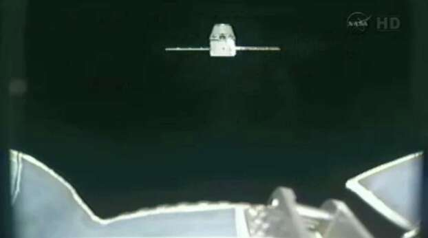 This image provided by NASA-TV shows the SpaceX Dragon commercial cargo craft taken from Canadarm2's video camera as Dragon approaches the International Space Station, Friday, May 25, 2012. In foreground is a portion of Canadarm2. Expedition 31 Flight Engineers Don Pettit and Andre Kuipers will use the Canadarm2 robotic arm to grapple the supply ship Friday morning with the berthing to the Earth-facing side of the station's Harmony node following. Dragon is scheduled to spend about a week docked with the station before returning to Earth on May 31 for retrieval. (AP Photo/NASA) Photo: Uncredited, Associated Press / NASA