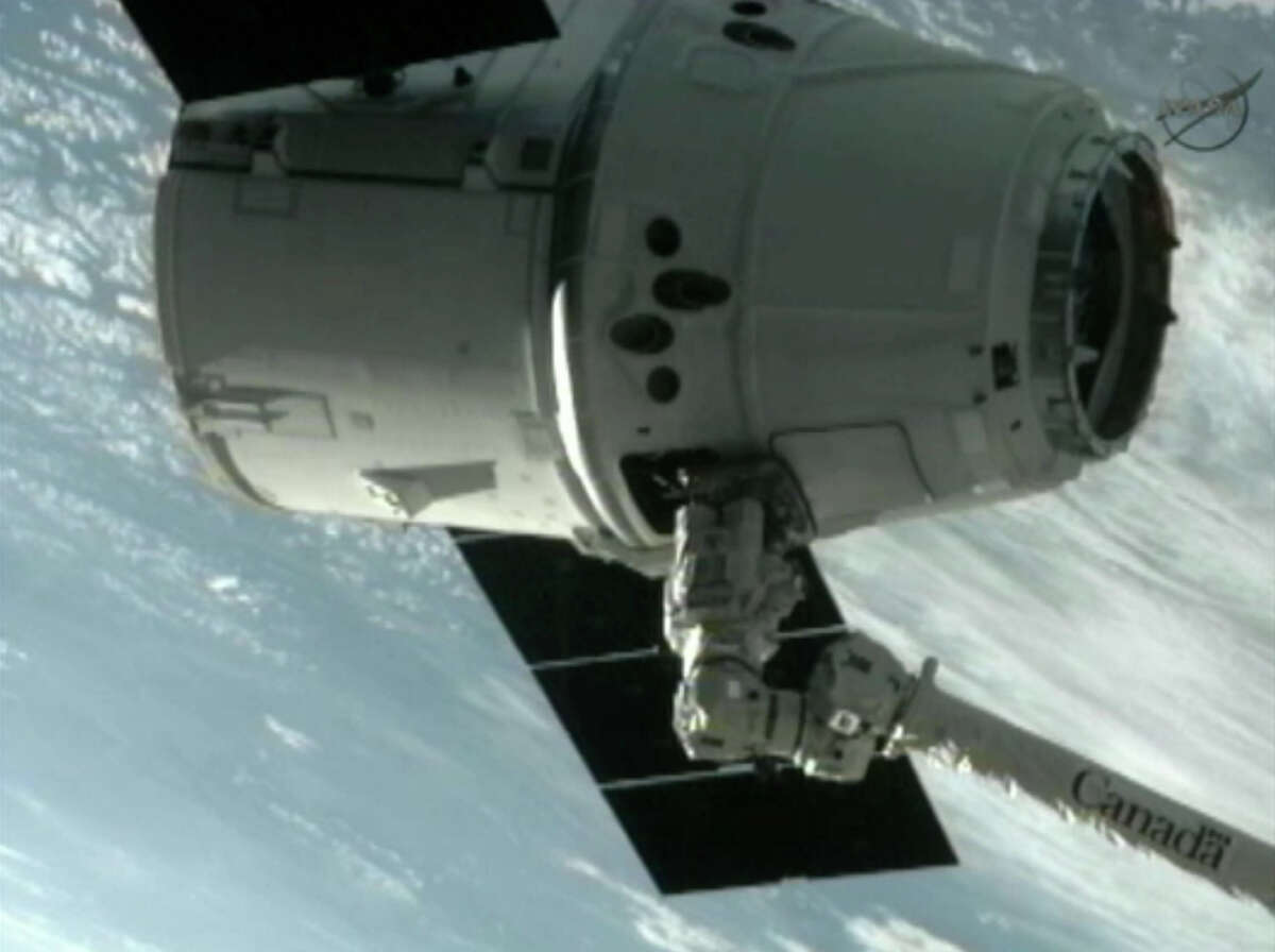 This image provided by NASA-TV shows the SpaceX Dragon commercial cargo craft after Dragon was grappled by the Canadarm2 robotic arm and connected to the International Space Station on Friday. Dragon is scheduled to spend about a week docked with the station before returning to Earth on May 31 for retrieval. (AP Photo/NASA)