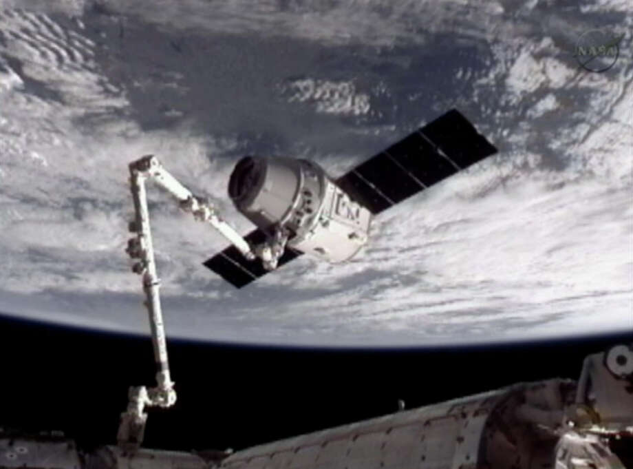 This image provided by NASA-TV shows the SpaceX Dragon commercial cargo craft, top, after Dragon was grappled by the Canadarm2 robotic arm and connected to the International Space Station on Friday,. Dragon is scheduled to spend about a week docked with the station before returning to Earth on May 31 for retrieval. (AP Photo/NASA) Photo: Associated Press