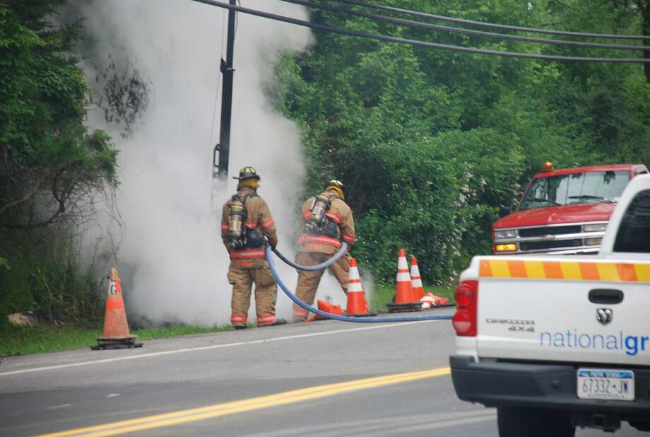 Firefighters extinguish flames after a light tower touched powerlines on Route 4 in East Greenbush, electrocuting a highway worker and igniting a fire. (Tom Heffernan Sr. / Special to the Times Union) Photo: Picasa