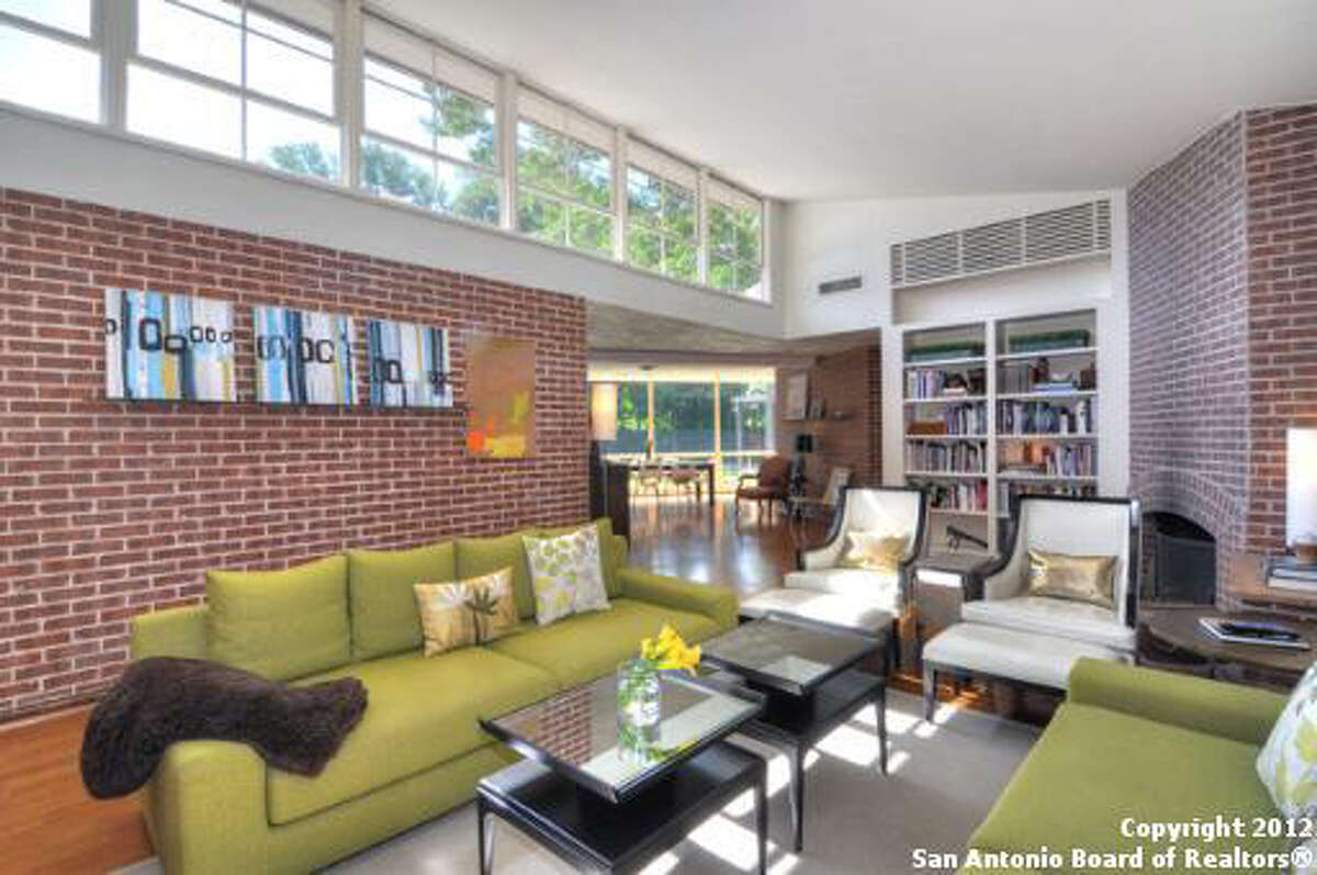 The living room features hardwood floors, built-in bookshelves, brick walls, and a brick fireplace.