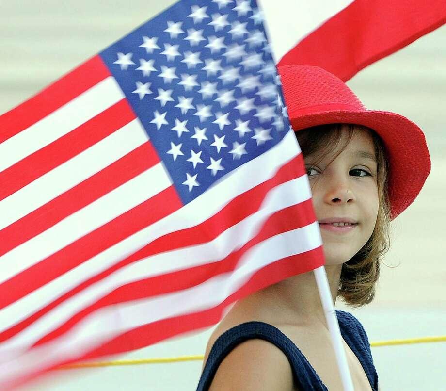 Madeline Ackley, 6, holds a U.S. flag. Photo: Charles Slate / The State