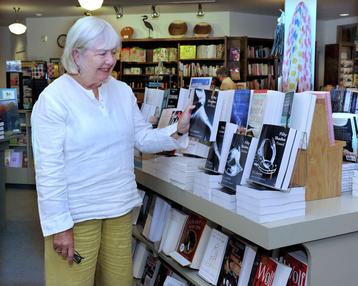 """Fran Keilty, owner of The Hickory Stick Bookshop in Washington Depot, stands near a display of E. L. James' trilogy, which incluses the titles """"Fifty Shades of Grey,"""" Fifty Shades Darker,"""" and """"Fifty Shades Freed,"""" in her bookstore Friday, May 25, 2012."""