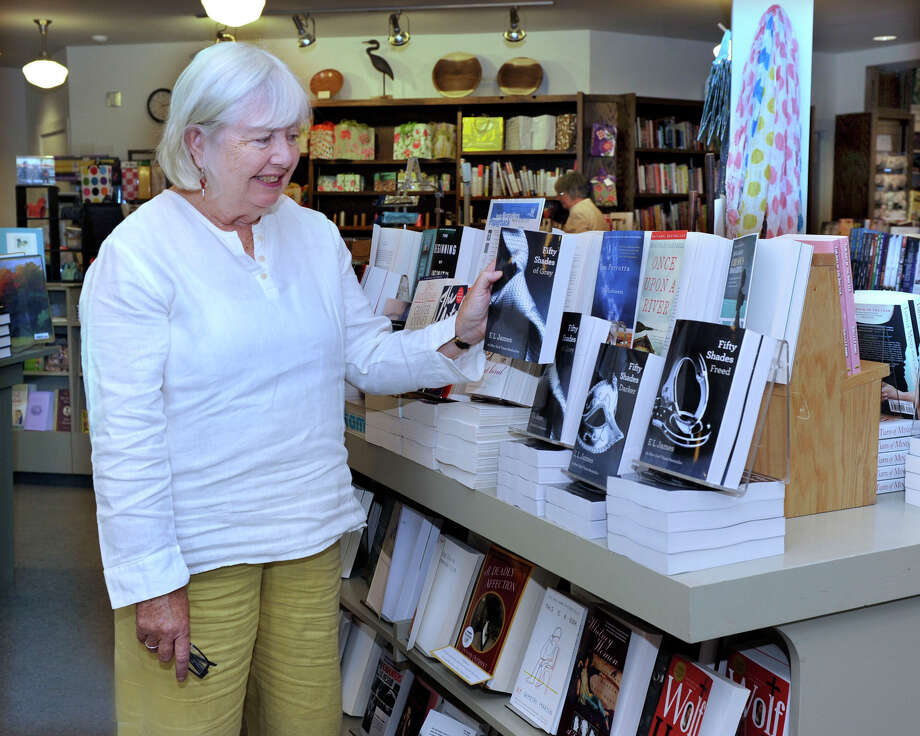 "Fran Keilty, owner of The Hickory Stick Bookshop in Washington Depot, stands near a display of E. L. James' trilogy, which incluses the titles ""Fifty Shades of Grey,"" Fifty Shades Darker,"" and ""Fifty Shades Freed,"" in her bookstore Friday, May 25, 2012. Photo: Carol Kaliff"