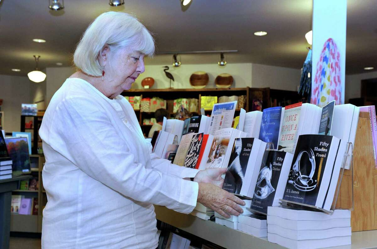 """Fran Keilty, owner of The Hickory Stick Bookshop in Washington Depot, stands near a display of E. L. James' trilogy, which includes the titles """"Fifty Shades of Grey,"""" Fifty Shades Darker,"""" and """"Fifty Shades Freed,"""" in her bookstore Friday, May 25, 2012."""