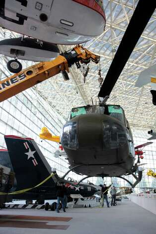 A crane lifts the Seattle Museum of Fight's 1970 Bell UH-1H 'Huey'  helicopter in the museum's main hall on May 25, 2012. Photo: Ted Huetter / The Museum of Flight, Seattle