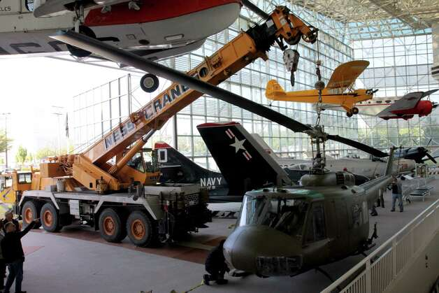 The Seattle Museum of Fight's 1970 Bell UH-1H 'Huey' is attached to a crane on May 25, 2012. Photo: Ted Huetter / The Museum of Flight, Seattle