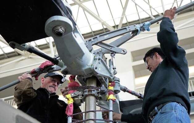 Workers attach a stabilizer bar to the Seattle Museum of Fight's 1970 Bell UH-1H 'Huey' while readying it for display on May 25, 2012. Photo: Ted Huetter / The Museum of Flight, Seattle