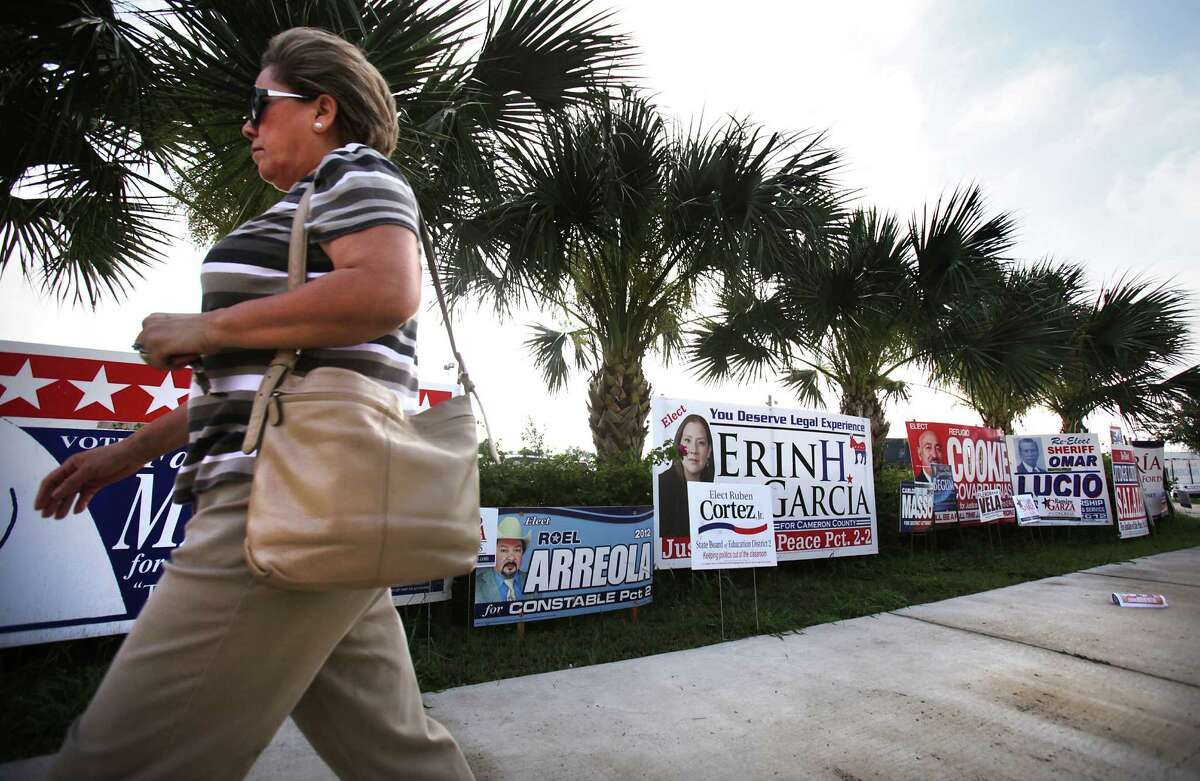A voter passes by political signs in front of the Cameron County Courthouse in Brownsville, TX, on her way to vote during early voting. Thursday, May 17, 2012. Photo/Bob Owen