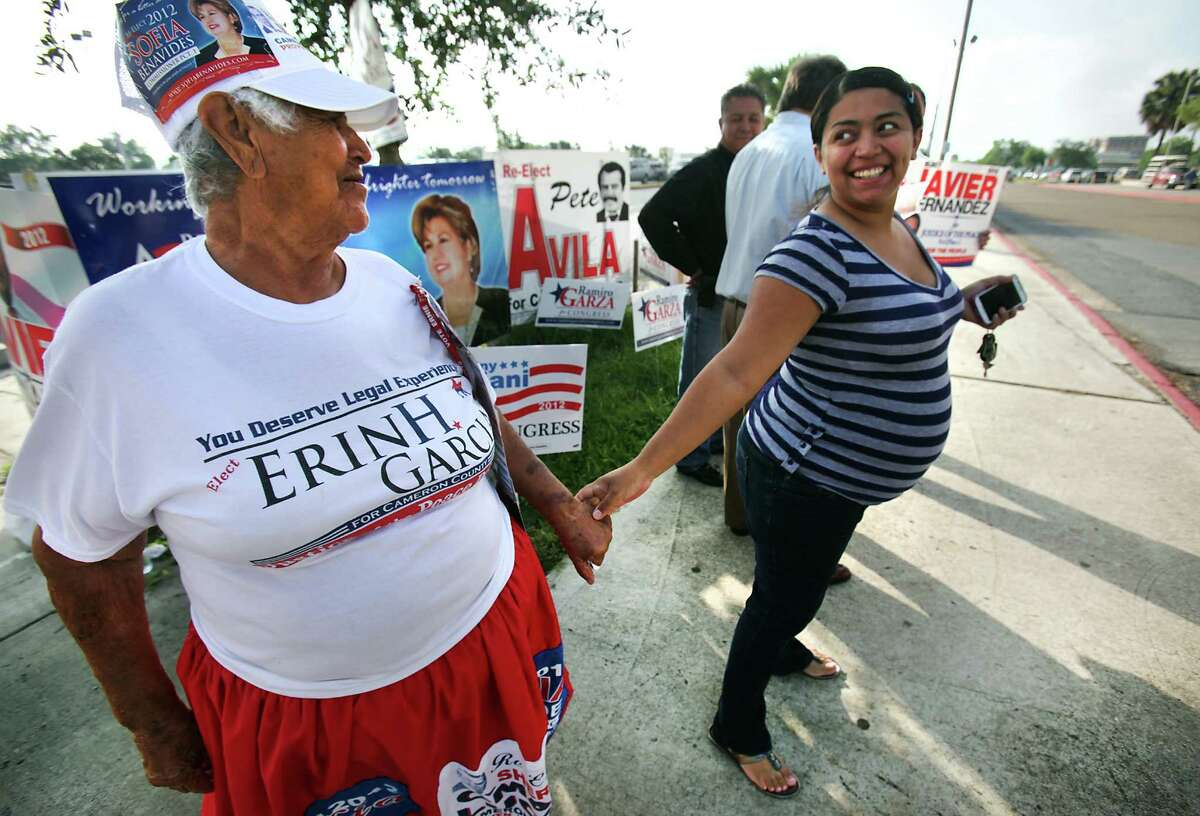 Herminia Becerra, left, the well known 83 year-old Politiquera in Brownsville, TX, is greeted by Amy Ramos, 32, who has received help from Becerra. Becerra was working a polling site in front of Cameron County Courthouse during early voting, as Ramos was on her way to vote. Thursday, May 17, 2012. Photo/Bob Owen