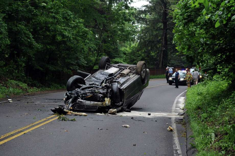 Police and firefighters stand at the scene on High Ridge Road near the New York border where the driver of a Toyota Highlander overturned the vehicle. Photo: Lindsay Niegelberg / Stamford Advocate